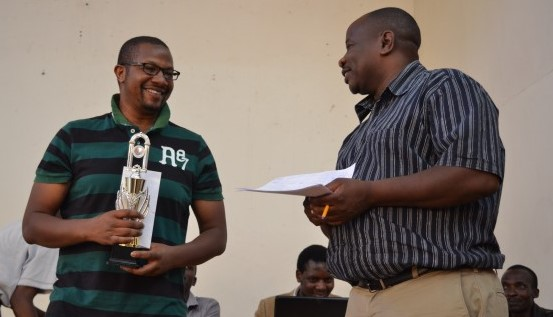 Ben Nguku (left) receives his trophy from CEO of Terrian Chess Academy Brian Kidula.