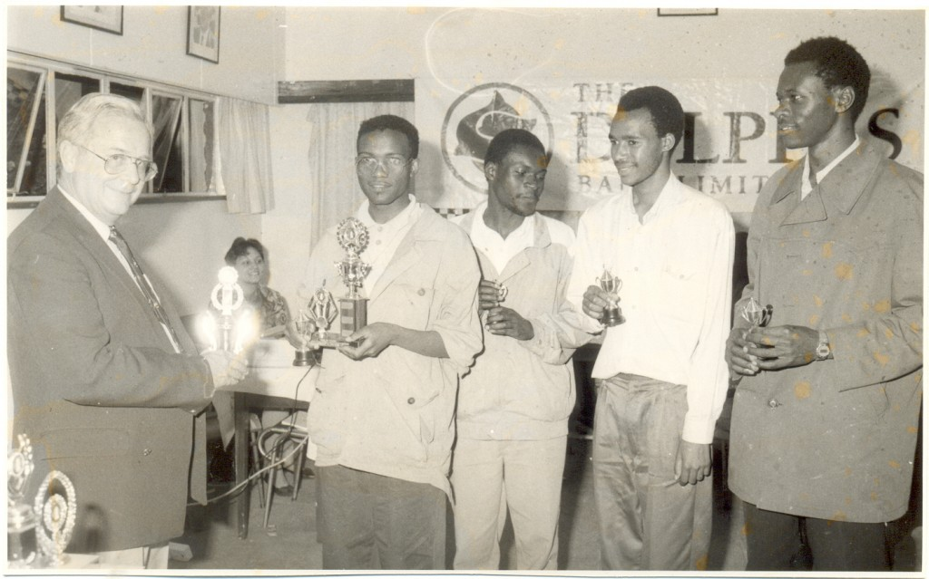 Blast from the past. The late MD of Delphis Bank (now Oriental Bank) Mr John Barnes present trophies to the winning team from Kenya Polytechnic. From left Philip Singe, Omele Mutanyi, Gatiti & Lewis Issaboke. Photo dated 27th October 1993. Venue YMCA Nairobi. Event Delphis Bank Championship.