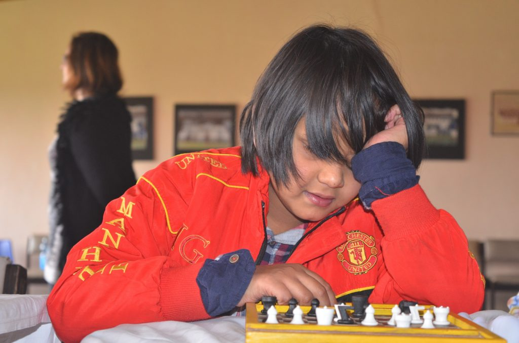 Sporting a Manchester United jacked Aditya Shah uses his special Braille chess set.