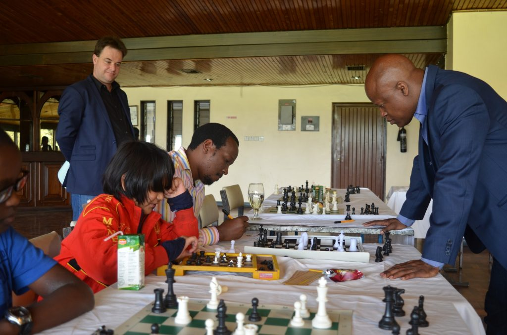 What move should I make. Aditya Shah v GM Maurice Ashely while KCFA Graham Jurgensen looks on and Githinji Hinga records the moves.