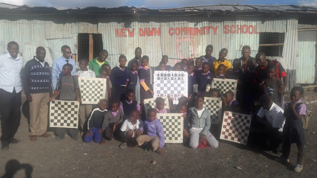 New Dawn Community School gets some chess equipment. IM Rodwell Makoto in red short on the right.