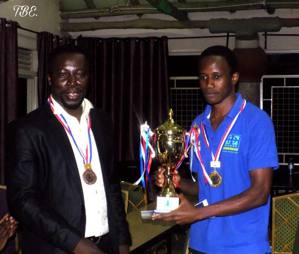 Uganda Chess Federation President Emmauel Mwaka (left) presents the trophy to FM Patrick Kawuma.