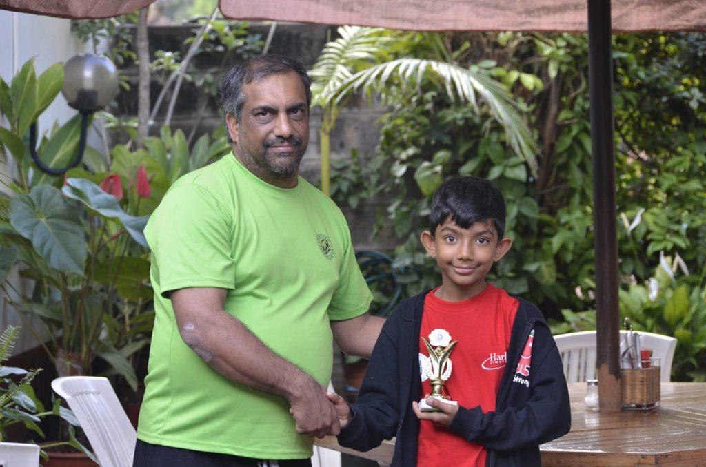 Reeyan Gosrani receives his trophy from Festival of Friendship founder Aneez Rahemtulla.
