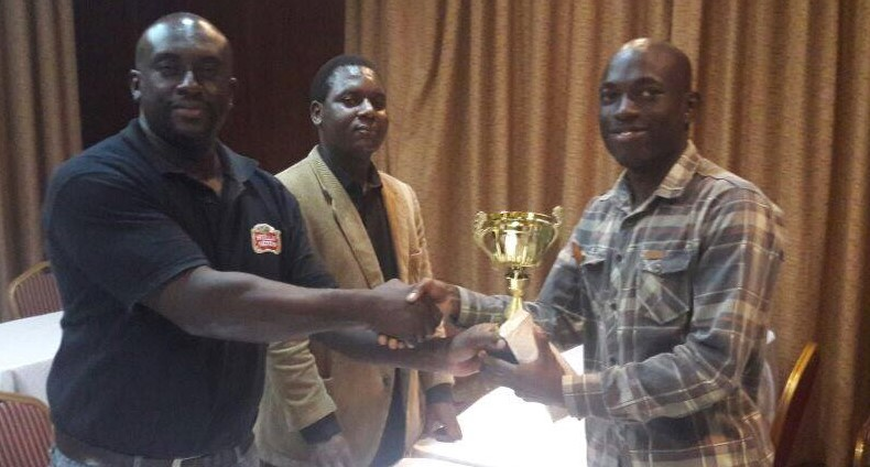 IM Elijah Emojong of Uganda (right) receives his trophy from Tanzania Chess Federation President Geoffrey Mwanika while Arbiter Duke Micheka looks on.