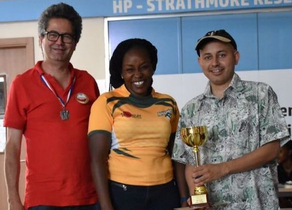 Sylvia Kamau - Starthmore University Sports Director middle presents the winner's trophy to Nairobi Chess Club players Willy Simons (left) and Mehul Gohil. Photo credit Allan Victor of Arongoey Photography.