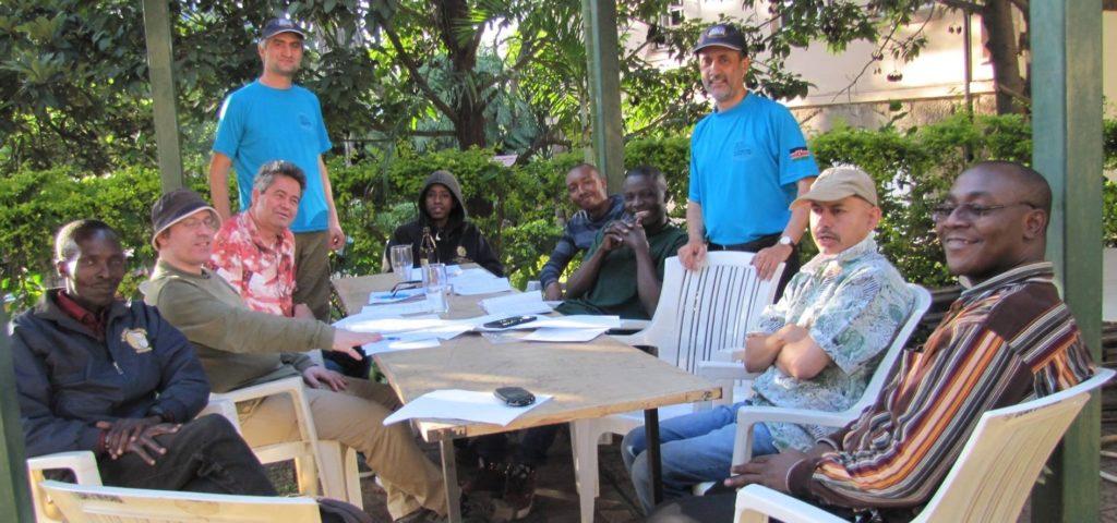 Photo of 60th AGM for Nairobi Chess Club. From left to right. Paul Oketch, Warren Pollock, Willy Simons, Mushfig Habilov (Misha with NCC shirt and cap), Ian Masaa, Ernest Thumbi, Paul Ochieng, Mehul Gohil, Kim Bhari (with shirt and cap) and Jackim Arigi