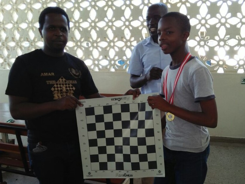 Top U18 Peter Njogu from Tumaini Children's Home (left) receives his prize.
