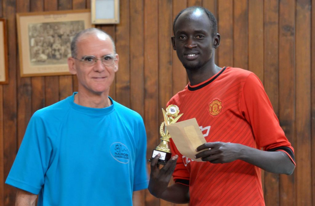James Panchol (right) receives his prize from Nairobi Chess Club Treasurer Roberto Villuela.