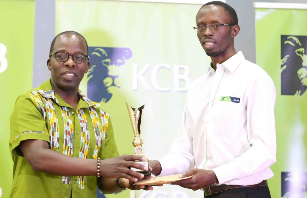 KCB Group Chief Operating Officer Samuel Makome (left) presents FM Harold Wanyama with his prize.