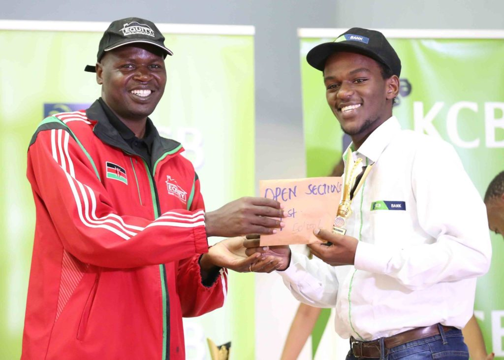 Chess Kenya Chairman Benard Wanjala (left) presents the top prize for the Challenger's section to a beaming Martin Njoroge.