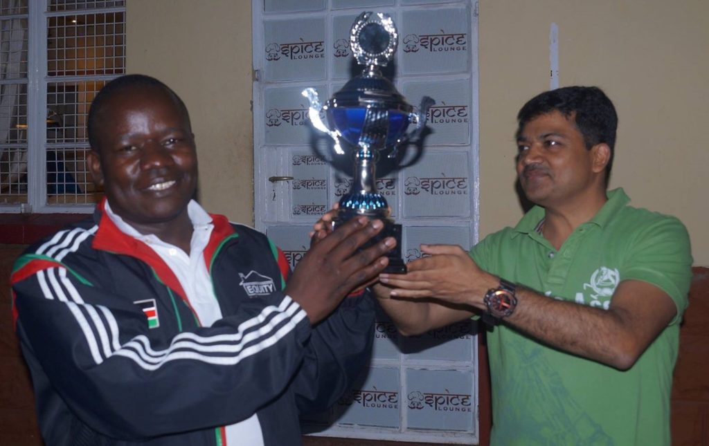 Proud winner FM Stephen Ouma receives his Elgon Cup trophy from Mr Reddy of MFI solutions.