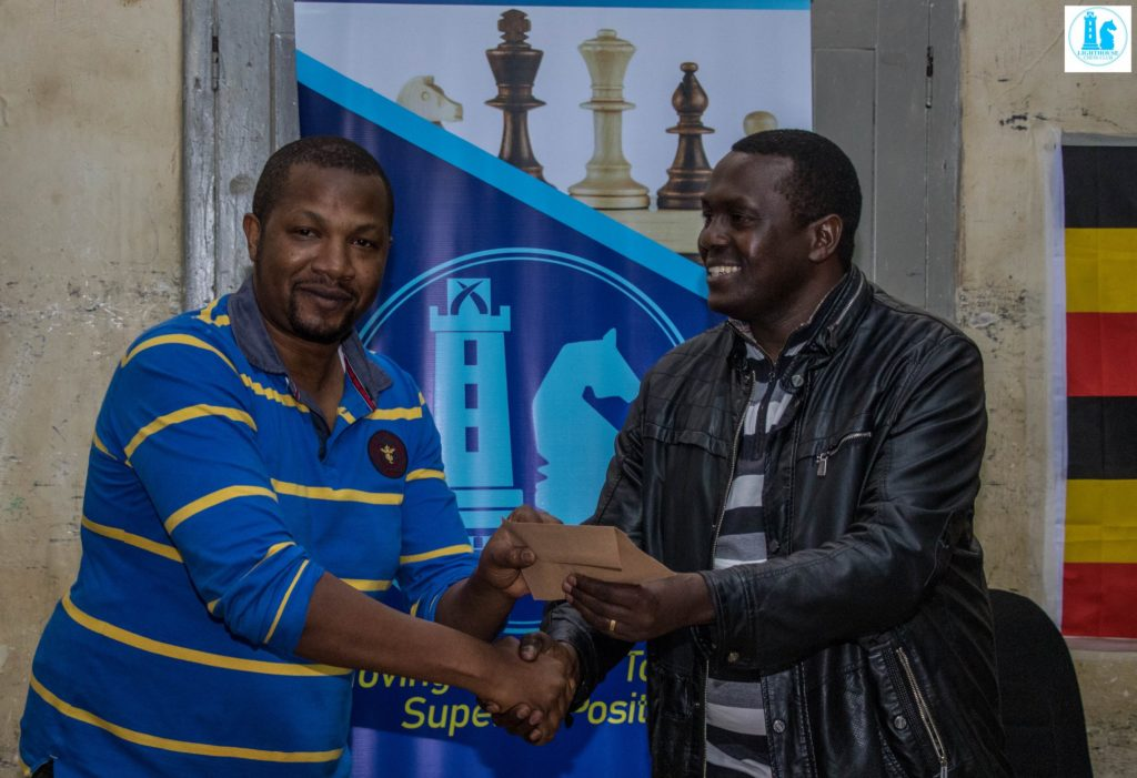 Ben Nguku (left) receives his prize from Mr Benjamin Musela.