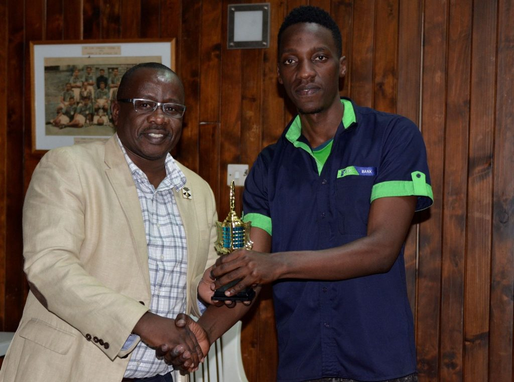 CEO Terrian Chess Academy (left) Local GM Brian Kidula presents FM Haruna Nsubuga with the winner's trophy.