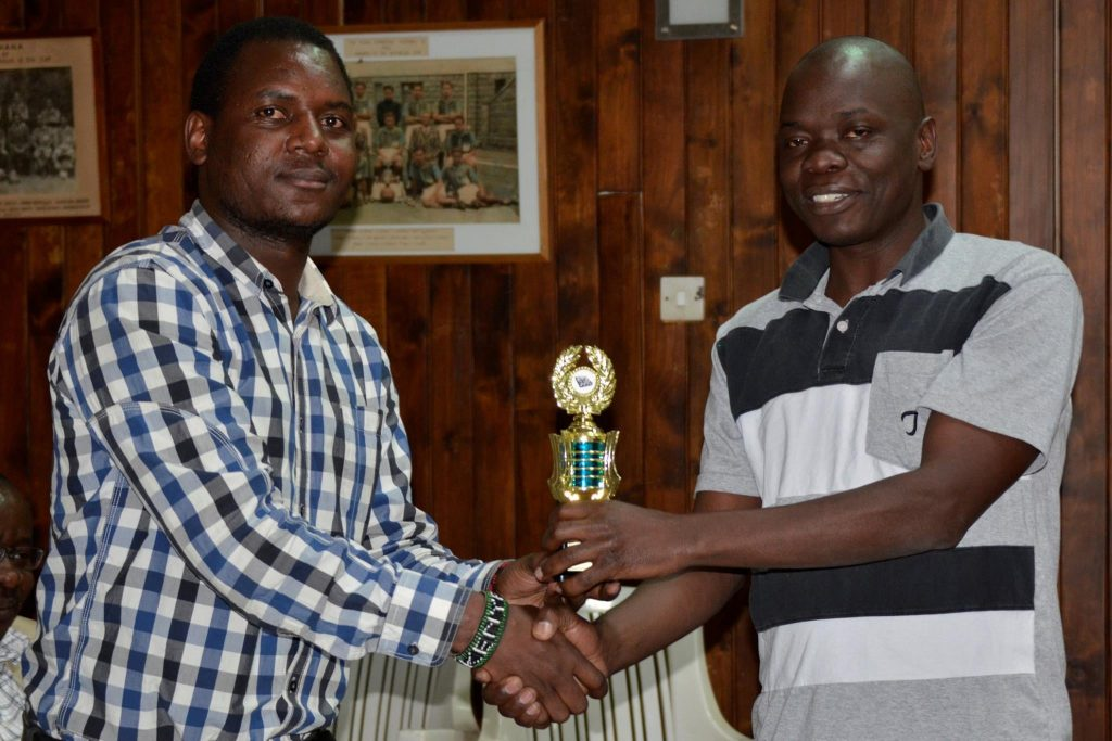 Chief Arbiter Duke Michieka (left) presents the winning trophy to Geoffrey Dokoria for winning the U1800 section.