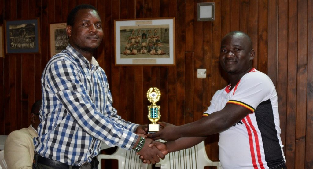 Chief Arbiter Duke Michieka presents John Vianney Muklazi with the winner's trophy for winning the U1600 section.
