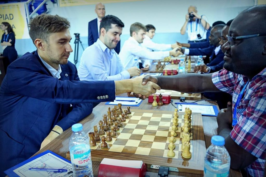 GM Sergey Karajkin shakes hands with IM Arthur Ssegwanyi of Uganda before the start of the round. Photo credit - Amruta Mokal ofChessbase India.