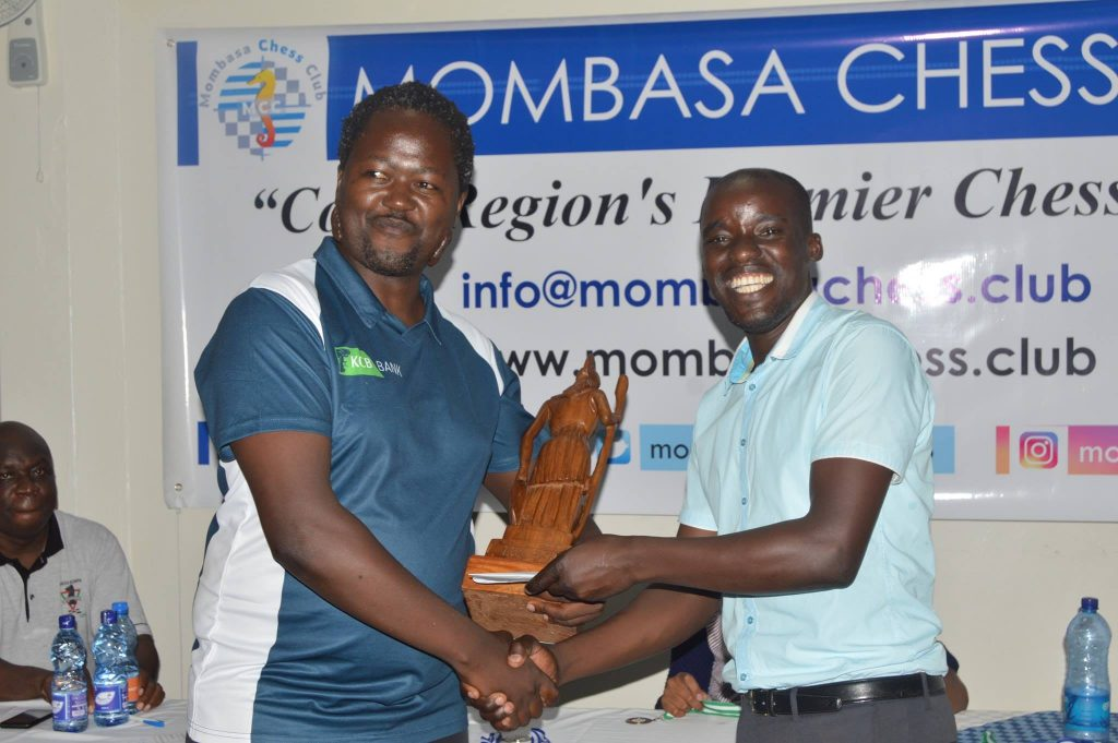 CM Ben Magana (left) receives the prize from Paul Ombui of Mombasa Chess Club. Photo credit Tony Kimani.