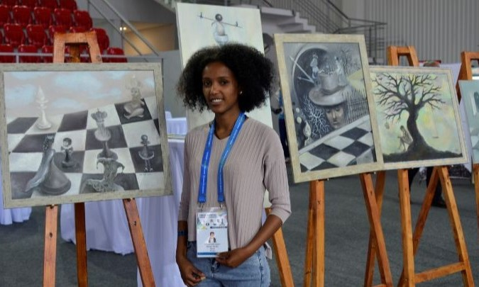 Ruth Eshetu Leykun from Ethiopia poses in front of some of the art works.