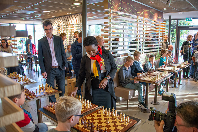 WFM Christine Namaganda plays a simultaneous while Tournament Director Loek van Wely looks on.Photo credit https://www.hoogeveenchess.nl/en.
