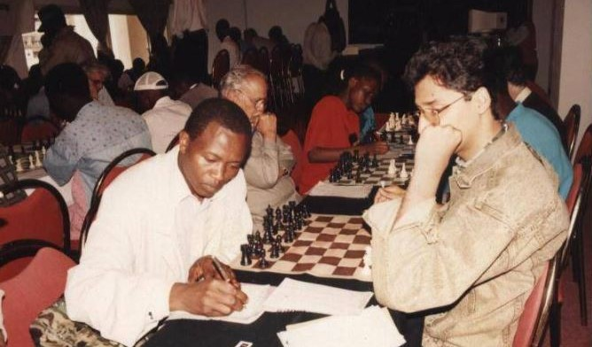 Photo from the 1995 CAL-IBM Kenya Open held at Grand Regency Hotel, Nairobi from 14th to 17th April 1995. Zahid Javaid (right with brown jacket) takes on unknown player. Diagonally opposite is the late Mohamed Younis Din father to sponsor of the event Dr Mujahid Din. Photo credit Zahid Javaid.