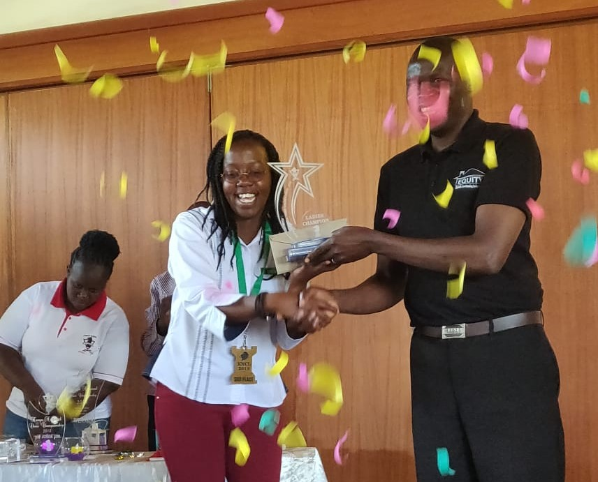 Kenya National Chess Champion Ladies - a delightful Gloria Jumba receives her trophy from Chess Kenya President Benard Wanjala. Photo credit Deep Gosrani.