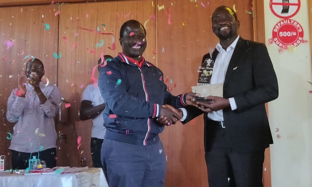 A burst of colour! - Gordon Oluoch who is the CEO of Kenya Academy of Sports presents the trophy to Dr Victor Ng'ani. Photo credit Deep Gosrani.