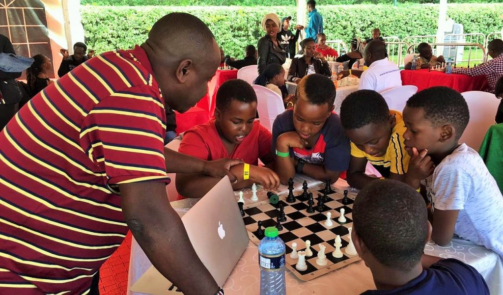 Local GM Brian Kidula taking some kids through the game of chess.