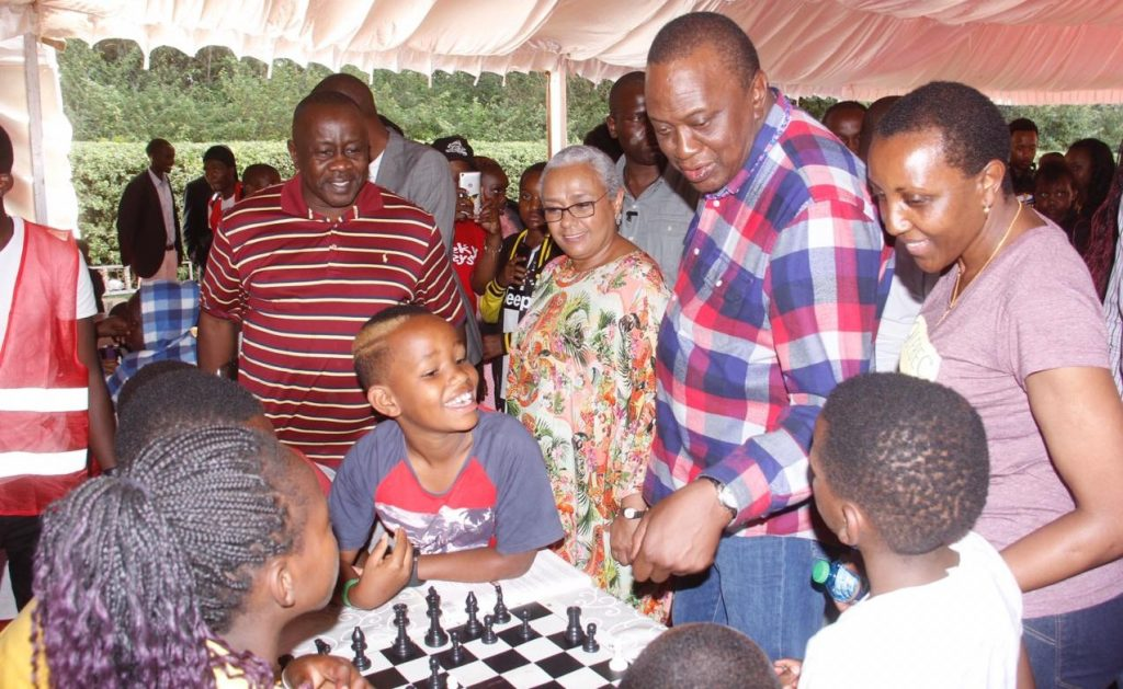 H.E President Kenyatta and First Lady Margaret Kenyatta interacts with chess players while Local GM Brian Kidula watches.
