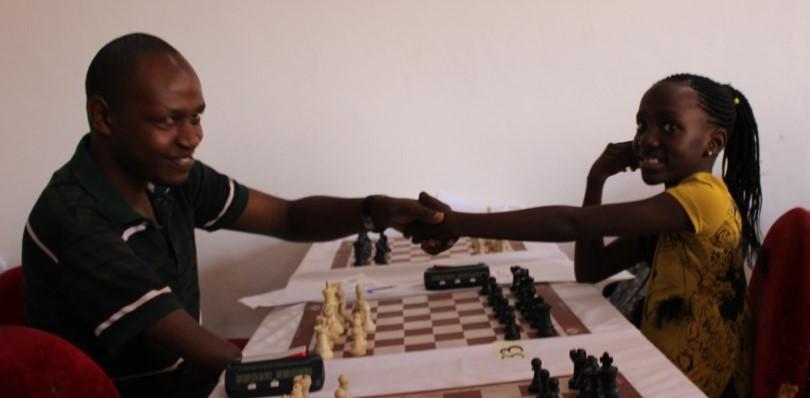 Ezekiel Masiko (left) shakes hands with 9 year old WCM Peace Naomi Nabuyondo.