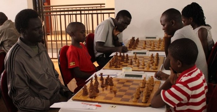 Vincent Buwule (left) in red shirt takes on Solomon Lubenga in a game that he won.