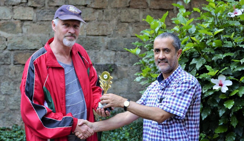 Peter Gilruth receives his trophy from Nairobi Chess Club Chairman Kim Bhari.