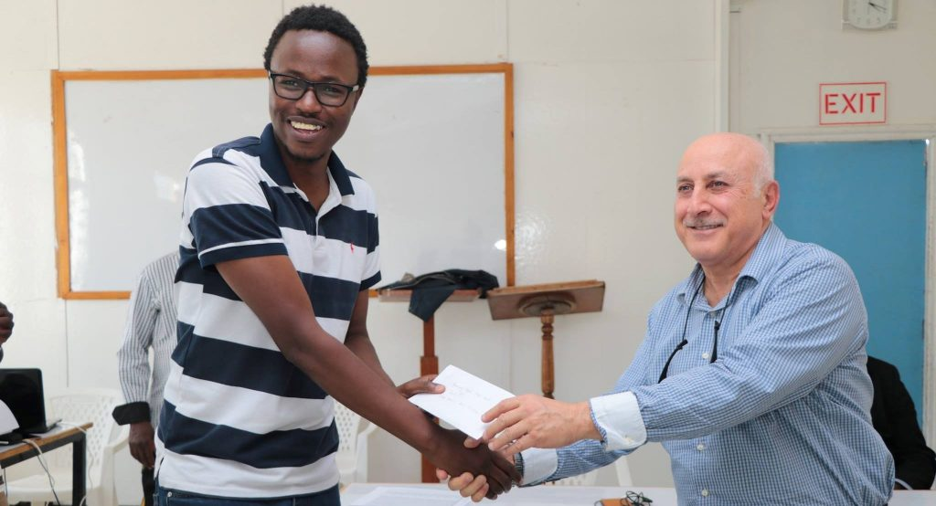 A happy Akello Atwoli receives his prize from Tunisian GM Slim Bouaziz.