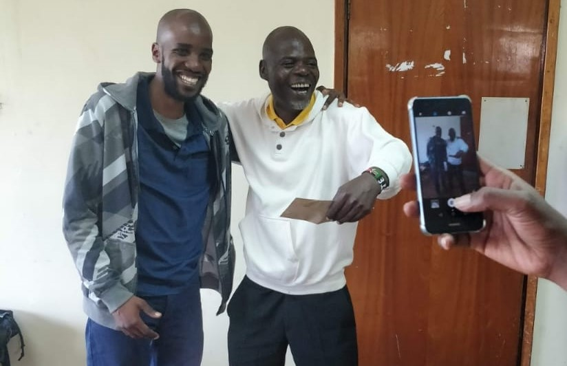 Martin Oyamo (white shirt) shows his joy at winning his prize from Solomon Thuo Anchor Chess Club.