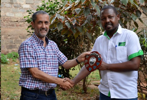 Chairman of Nairobi Chess Club Kim Bhari (left) presents Ricky Sang with the winner's shield.