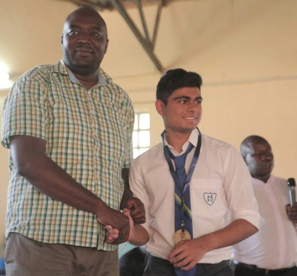 Nyeri County Assembly Deputy speaker Hon. Samuel Kariuki presents Dev Shah with his prize during the closing ceremony of the 2019 KNYCC.
