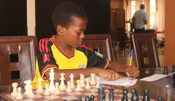 Another budding Ugandan player carefully records his move.  Photo credit James Mwangi.