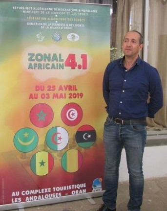 Nabil Doghri the chess coach of Tunisia poses next to the poster of the event.  Photo credit Federation Algerienne des Echecs.