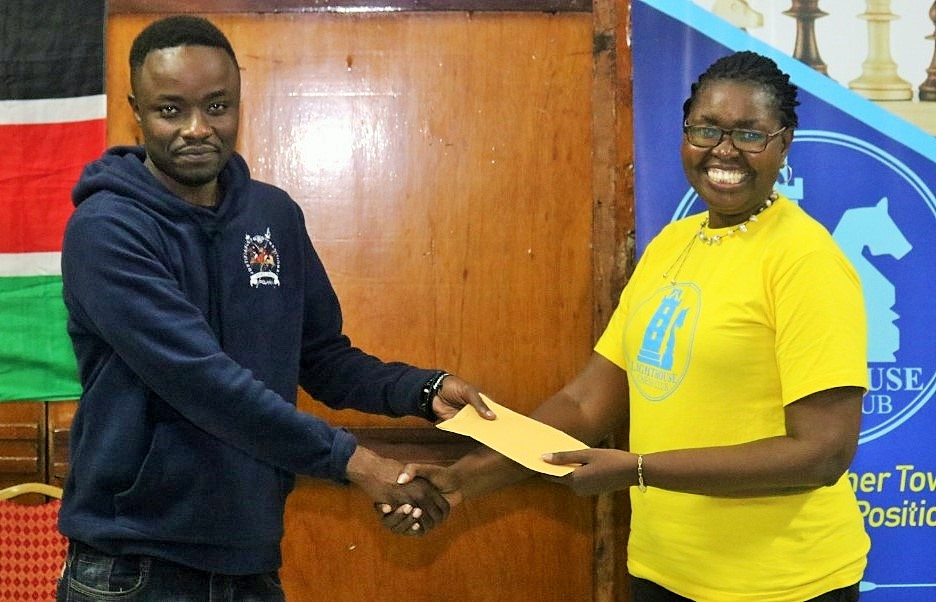 Joseph Methu receives his prize from Judy Kiragu of Lighthouse Chess Club.