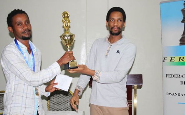 President of Rwanda Chess Federation Kevin Gwanza (right) presents the winning trophy for the Open section to the winner Eugene Mugema of Rwanda.