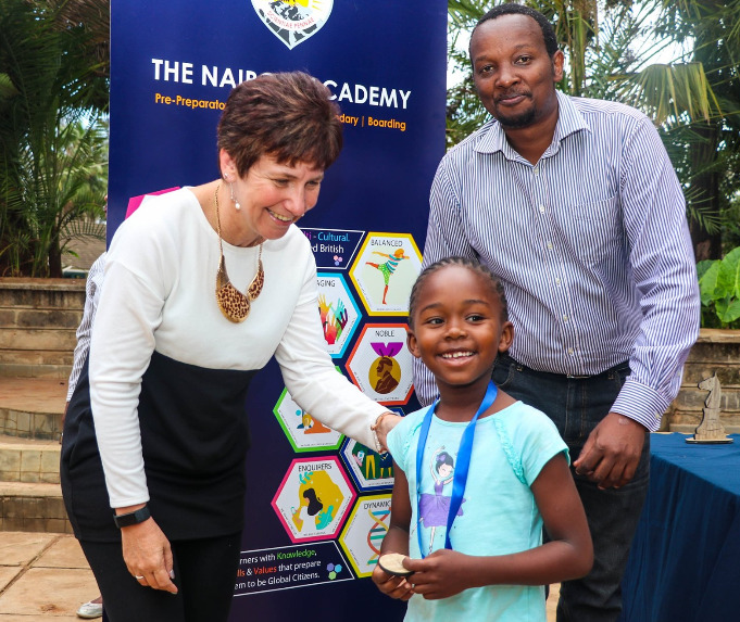 Ms Dorena Maina presents a prize to a winner while Githinji Hinga of Mini Chess Kenya looks on.  Photo credit Hawi Eliakim.