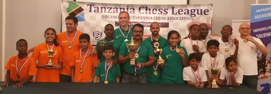 All the prize winners pose for a historic photo. Flashnet Chess Club in orange uniform (3rd place), Ahead Africa Chess Club in green uniform (winners) and Don Bosco Chess Club (2nd place).