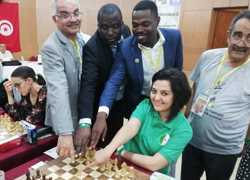 WIM Amina Mezioud of Algeria (sitting with green shirt) makes her first move. Photo credit Amira Marzouk.