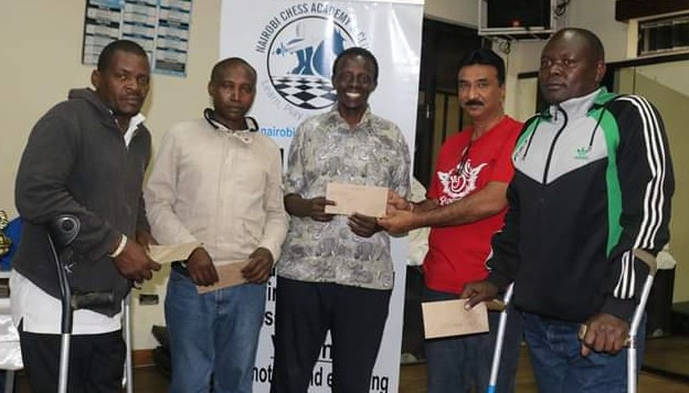Some of the members from the Kenya Para Team at the 2019 Nairobi Open Chess Tournament receiving a prize from Ameet Parikh (in red shirt). From left Alfred Simiyu Barasa, Edwin Muruah, Dennis Muga and Geoffrey Maoga Mosongoh.
