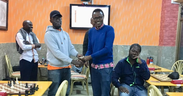 Ronald Bolo presents the winner Joseph Atwoli with the top prize of KES 30,000.