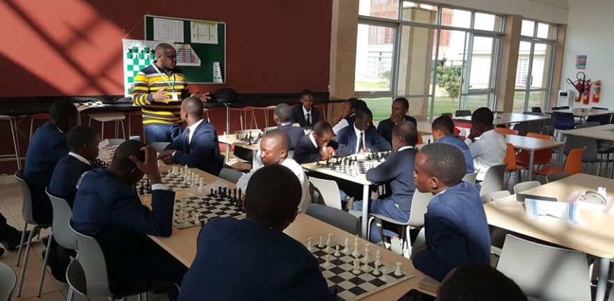 Brian Kidula CEO of Terrian Chess Academy taking students of the M-Pesa Foundation Academy through a chess class.