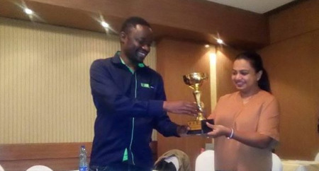 Joseph Methu (left) receives his trophy from Mrs. Sapna Bhatt Director of Rising Star Academy who was one of the sponsors. Photo credit Emmanuel Mwaisumbe.