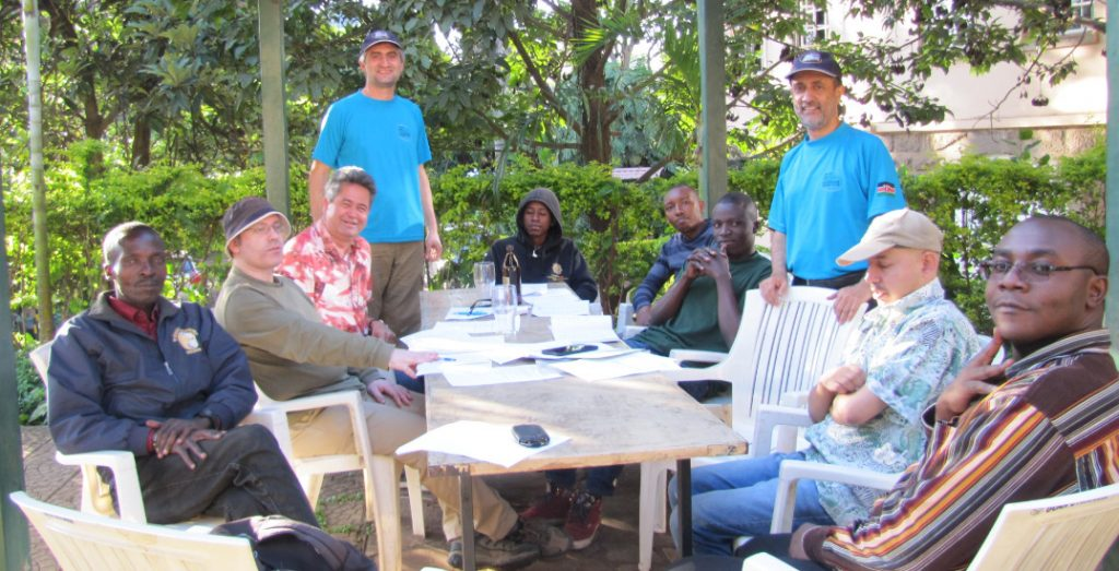 Photo of 60th Annual General Meeting for Nairobi Chess Club. From left to right. Paul Oketch, Warren Pollock, Willy Simons, Mushfig Habilov (Misha with NCC shirt and cap), Ian Masaa, Ernest Thumbi, Paul Ochieng, Mehul Gohil, Kim Bhari (with shirt and cap) and Jackim Arigi