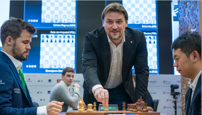 Dmitri Bulykin makes the first move in the Carlsen - Hao game.