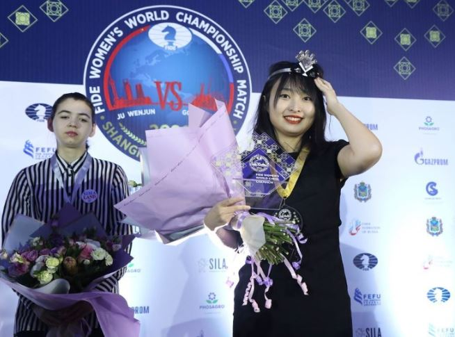 World Champion Ju Wenjun poses with her crown and prize while Challenger Aleksandra Goryachkina looks on.