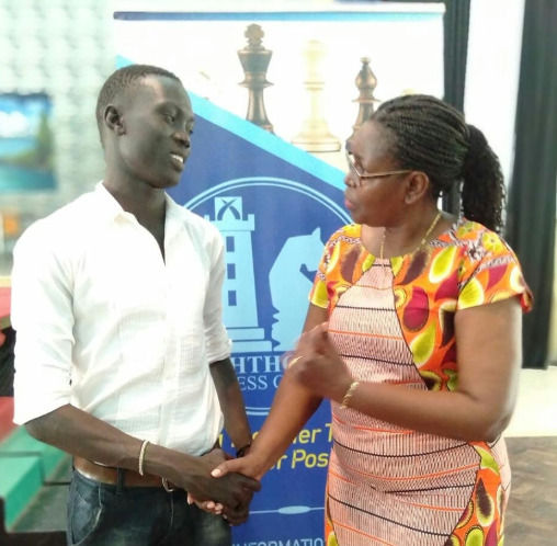 John Thon Ngony the winner of the event is congratulated by Judy Kiragu of Lighthouse Chess Club.